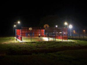 il y a un terrain de sport éclairé avec des lampadaires solaires solamaz avec des enfants qui jouent le soir au football